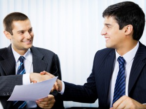 Businesspeople, or businessman and client, with document